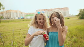 Two girls on a city background blow soap bubbles stock video footage