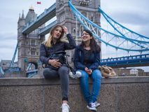 Two girls on a city trip to London - relax at the Tower Bridge stock photo