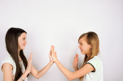 Two girls claping palms royalty free stock image