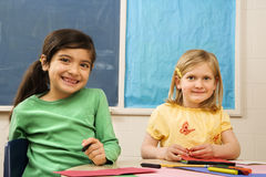 Two Girls in Classroom. Two young girls in classroom with art and drawing materials Stock Photos