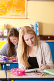 Two girls in the classroom. Two teenage girls in the classroom doing their homework Stock Images