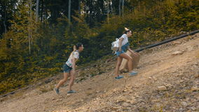 Two girls climb the mountain on a steep slope. Two girls on a sunny day climbing the steep slope of the mountain, in the middle of the forest stock footage