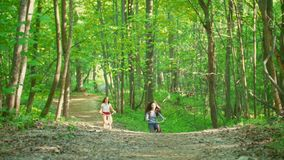 Two girls climb the path to the hill in the green forest, one girl falls, summer day. Telephoto shot stock video footage
