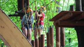 Two girls climbing in rope park. MOSCOW, RUSSIA - JULY, 29, 2015: Two girls climbing in rope park stock video