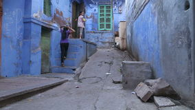 Two girls climbing on stairs in front of a house on the street of Jodhpur. JODHPUR, INDIA - 5 FEBRUARY 2015: Two girls climbing on stairs in front of a house on stock footage