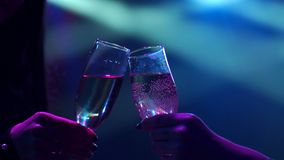 Two girls clink glasses of champagne at a party. Close-up of the hand of the girls with glasses of champagne at a party in the dark with bright spotlights of stock video footage