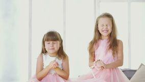 Magic - two little girls dream of a gift. Two girls close their eyes and make a wish, and then blow on the snow and laugh stock footage