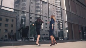 Two girls in the clothing business is happy, jumping and having fun. business woman celebrating success and victory. Silhouettes of business women who rejoice in stock video