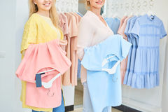 Two girls with in a clothing store Stock Photos