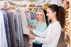 Two girls at clothing store. Two joyful smiling girls selecting basic garments at clothing store Royalty Free Stock Images