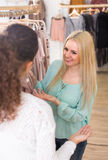Two girls at clothing store. Two ordinary female friends selecting basic garments at the store and smiling Royalty Free Stock Photography