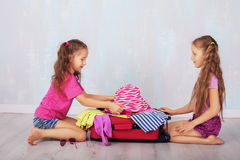 Two girls collect a suitcase on a journey. Children are going to travel stock photography