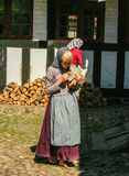 Two girls  collecting firewood in traditional clothes  at the gamle by of Ahrus. AT AARHUS - ON 07/27/2008   two girls collecting firewood   in traditional Royalty Free Stock Images