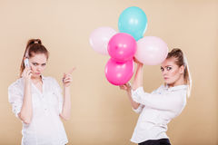 Two girls with mobile phone and balloons. Two girls with colorful balloons and mobile phone. Best friends preparing party celebration, having problem, bad Stock Photography