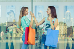 Two girls with colorful shopping bags. High five. Sales season. Stock Images