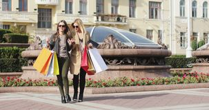 Two girls are with colorful shopping bags talking and laughing on the street. Blonde and brunette fashion women meet each other in the city center after stock video footage