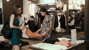 Two girls come to the store and choose blouses. Two young girls make shopping stock video footage