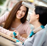 Two girls communicate sitting at the desk Royalty Free Stock Photos