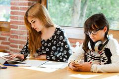 Two girls concentrating with schoolwork. Royalty Free Stock Images