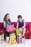 Two girls consider and show each other purchases Stock Photography