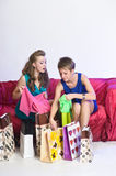 Two girls consider and show each other purchases Royalty Free Stock Photos