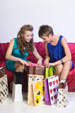 Two girls consider and show each other purchases Royalty Free Stock Image