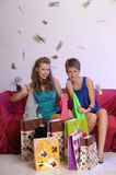 Two girls consider and show each other purchases Stock Photos