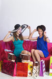 Two girls consider and show each other purchases Royalty Free Stock Images