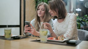 Two girls are considering something on smartphone. While sitting with sushi rolls and mojito in asian restaurant stock footage