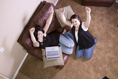 Two Girls on the Couch Shopping Online Royalty Free Stock Photography
