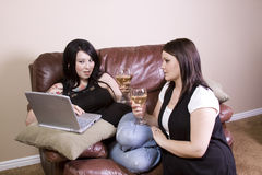 Two Girls on the Couch Shopping Online Stock Image