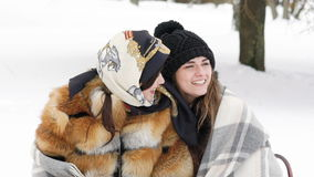Two girls covered in plaid embracing and smiling in the winter park. Slowly stock footage