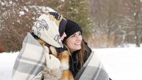 Two girls covered in plaid smiling in the winter park. Slow motion stock video footage