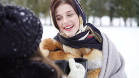 Two girls covered in plaid speaking, smiling and drinking tea in winter park 4K.  stock footage