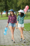 Two girls in cowboy hats with balloons Royalty Free Stock Photography