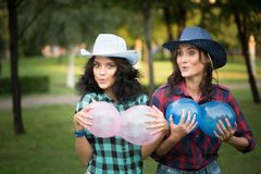 Two girls in cowboy hats with balloons Stock Photos
