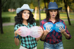 Two girls in cowboy hats with balloons Royalty Free Stock Image
