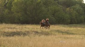 Two girls riding horses in field at sunset, slow. stock video footage