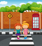 Two girls crossing the road Stock Photography