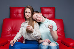 Two girls with cups of coffee sitting together Stock Photo