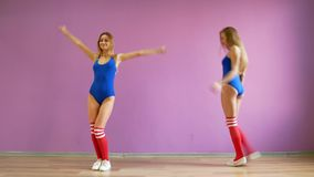 Two girls dance modern dances. Women in swimsuits and leg warmers.  stock video footage