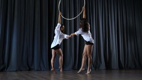 Two girls are dancing with aerial hoop on stage stock footage