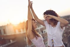 Two girls dancing on the building rooftop. Two girls dancing on a building rooftop at sunset, affectionate and happy, with cityscape in the background stock image