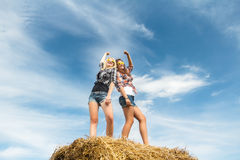 Two girls dancing in full length on straw bale Stock Images