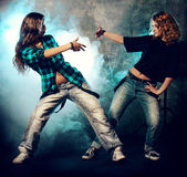 Two girls dancing. Modern hip-hop dancers over grunge background. Urban, disco style Royalty Free Stock Photo