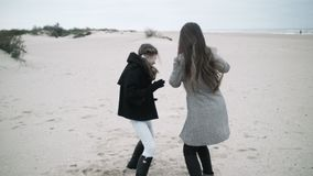 Two girls are dancing outdoors. Two girlfriends are dancing on the beach. Sisters have fun on a walk. Camera around stock video
