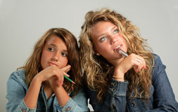 Two girls daydreaming. Two girls looking up and to the side, holding pen or pencil, thinking or daydreaming Stock Photo
