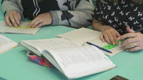 Two girls deciding the home task in a notebook. Two girls sitting at the school desk deciding the home task in a notebook at the school stock footage