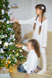 Two girls decorate the Christmas tree Royalty Free Stock Photos
