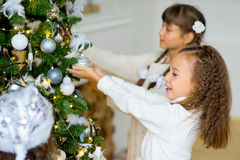 Two girls decorate the Christmas tree Stock Photos